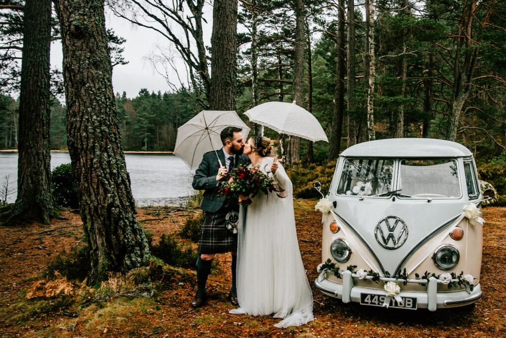 bride and groom kissing beside VW wedding campervan at Glen Tanar Deeside Classic Campers